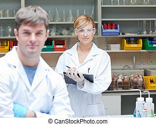 dois, afirmativo, cientistas, olhando câmera, ficar