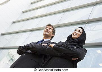 dois, businesspeople, ficar, ao ar livre, por, predios, sorrindo, (selective, focus)
