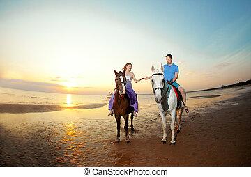dois, cavaleiros, ligado, horseback, em, pôr do sol, ligado, a, praia., amantes, passeio, hors