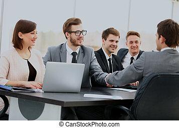 dois, confiante, homens negócios, handshaking, e, sorrindo, enquanto, sentar tabela, junto, com, seu, colegas.