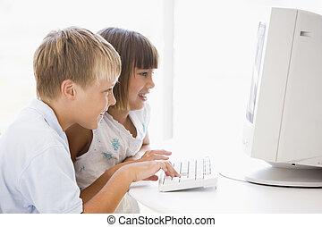 dois, filhos jovens, em, escritório lar, com, computador, sorrindo