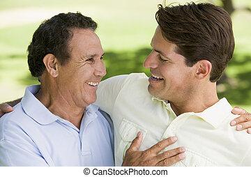 dois homens, ficar, ao ar livre, ligar, e, sorrindo