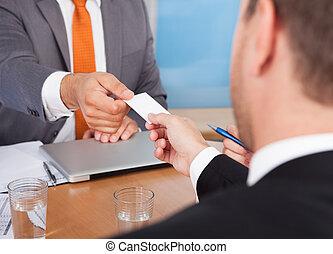 dois, homens negócios, segurando, cartão, cima escrivaninha
