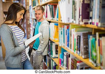 dois, jovem, estudantes, por, estante, em, a, biblioteca