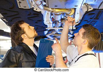 dois, mecanica, em, work., dois, confiante, auto mecânico, trabalhar, a, loja reparo, e, discutir, algo, enquanto, um, de, lhes, prendendo uma prancheta