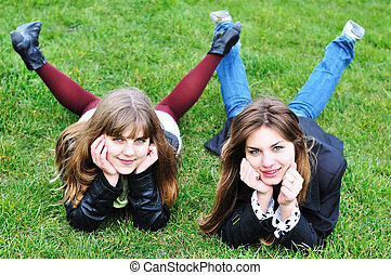 dois, meninas adolescentes, deitando, grama