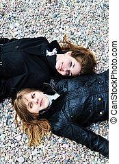 dois, meninas adolescentes, deitando, ligado, a, seixo