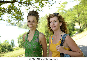 dois, mulheres jovens, andar, por, a, lago