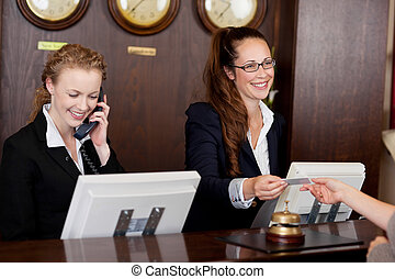 dois, recepcionistas, em, um, escrivaninha recepção