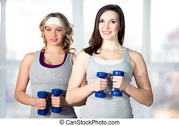 dois, sporty, jovem, fêmeas, fazendo, lado, curvas, com, dumbbells