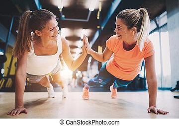 dois, sporty, meninas, fazendo, empurrão, ups, em, ginásio