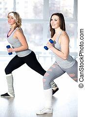 dois, sporty, mulheres jovens, fazendo, aeróbica, com, dumbbells