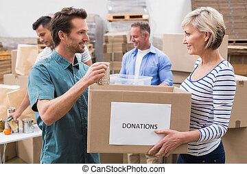 dois, voluntários, segurando, um, doações, caixa