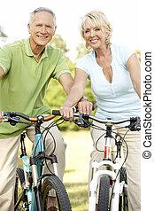 dojrzała para, jeżdżenie rowery