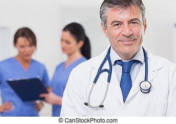 doktor z stetoskopem, uśmiechanie się, i, jego, drużyna, za, jemu