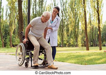 doktoren, hjælper, den, patient, til få, oppe, af, den, wheelchair, og, gang
