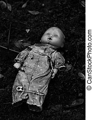an abandonned doll with pins on a tomb in a cimetarry
