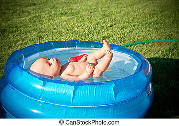 doll floating in the small pool - a small doll floating in...