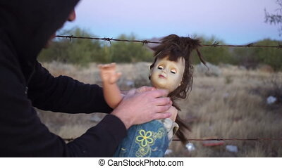 Weird scene of a lunatic crazy man full of rage and violence while choking an old toy doll hanging outside on a barbed wire fence.