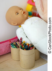 Doll next to crayons