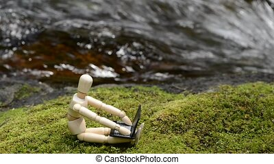 Wooden doll operating a laptop on a green moss in front of brook
