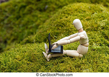 Doll operating a laptop - Wooden doll operating a laptop on ...
