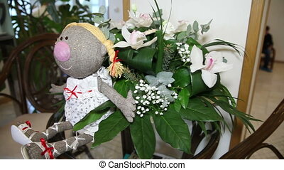 Doll with flowers on the table