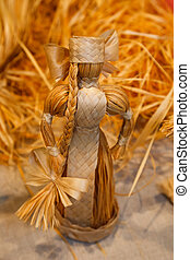 Doll woven from straw. Antique toys, souvenirs. Close-up.