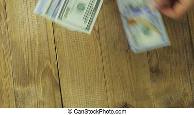 Dollar Banknotes Falling on a Wooden Table - Dollars...