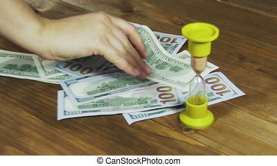 Dollar Banknotes Falling on a Wooden Table and Hourglass