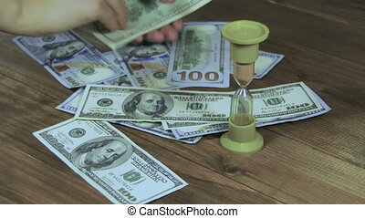 Dollar Banknotes Falling on a Wooden Table and Hourglass -...
