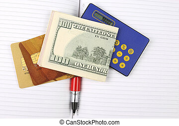 dollar bills, calculator, cards and pen lying on a notebook