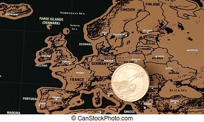 dollar coin on black scratch travel map of Europe, EU