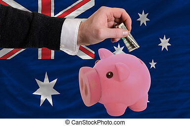 dollar into piggy rich bank and national flag of australia