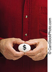 Dollar sign ($) written on egg held by man