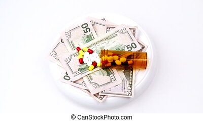 Dollars and pills turning against white background