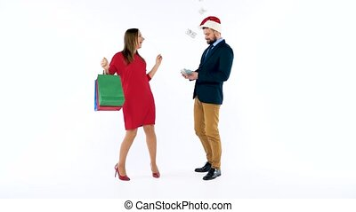 Dollars falling on formally dressed man and woman in the Santa Claus hat. Let's go holiday shopping and celebrate concept.