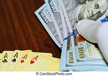 Dollars holded in hand over the poker playing cards