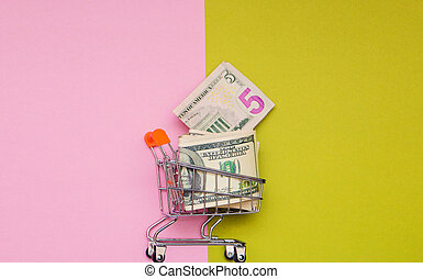 dollars money in shopping cart on green pink background with copy space