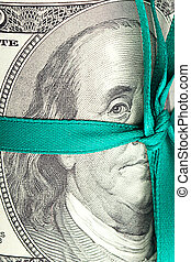 Dollars rolled into a tube tied with ribbon