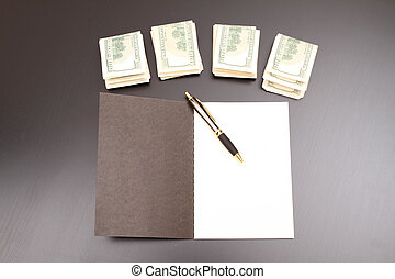 Lots of dollars with an open copybook