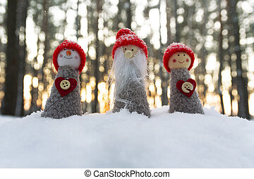 Dolls gnome in red caps on the background of snow. Christmas miracles
