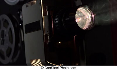 Vintage 16 mm movie projector projecting film in a dark room tracking shot