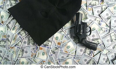 Dolly: Balaclava and gun on pile of $100 american dollar...