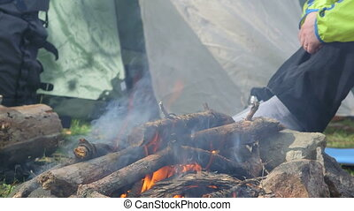 Dolly: Campfire - Female traveler sitting by campfire in the...