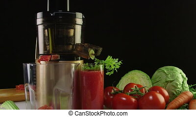 Dolly: Fresh squeezed tomato juice with cold press juicer on a black background