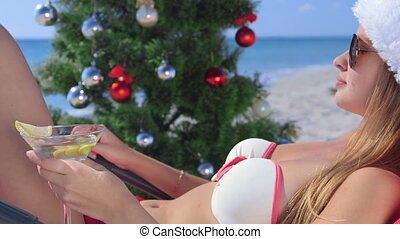 Dolly: Girl in Santa hat with martini glass relaxing on tropical beach