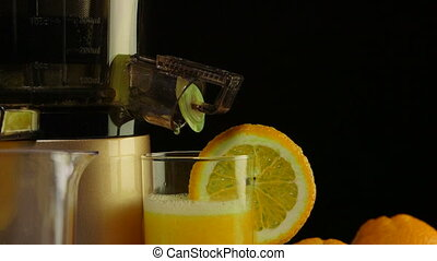 Dolly: Glass of freshly squeezed fruit juice from orange with masticating juicer
