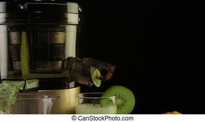 Dolly: Glass of freshly squeezed fruit juice from orange and kiwi using masticating juicer