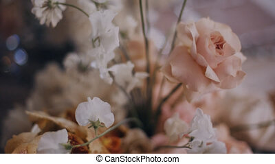 Dolly in shot of beautiful peach colour floristic composition on wedding table